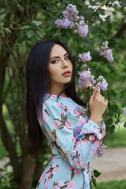 Brunette woman in the branches of a beautiful flowering tree. Premium Photo