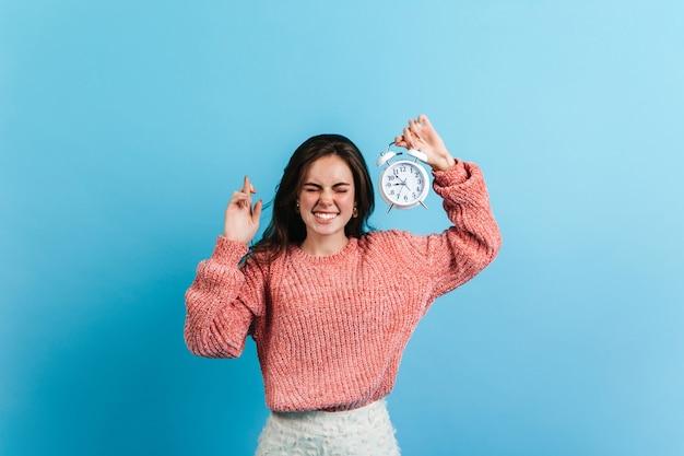 Donna castana ha incrociato le dita e tiene la sveglia bianca. modello in maglione oversize in posa sulla parete blu. Foto Gratuite