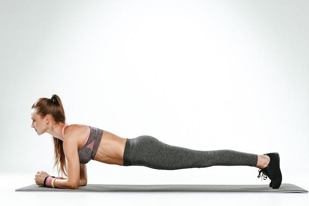 ジムでいくつかのストレッチ体操を行うブルネットの女性 無料写真