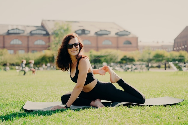 Brunette woman dressed in sportswear working out outside Premium Photo