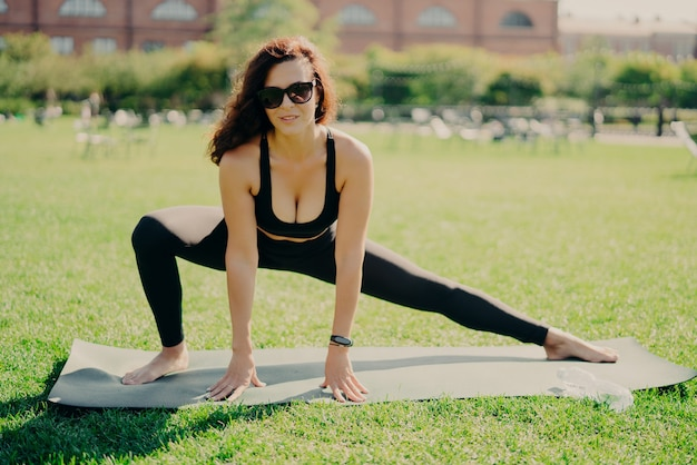 Brunette woman dressed in sportswear working out outside Premium Photo