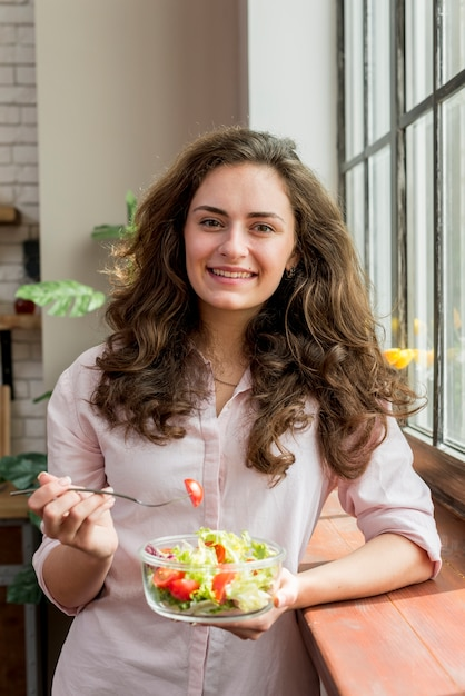 Brunette woman eating a salad Free Photo