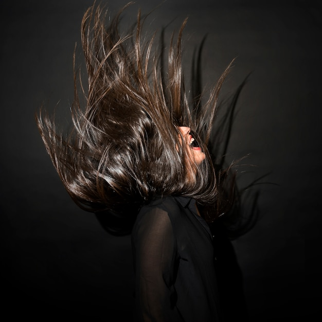 Brunette woman in evening wear with windy hairs Free Photo