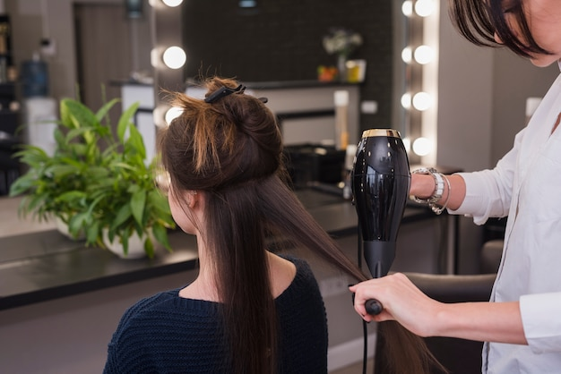 Brunette woman getting her hair done Free Photo
