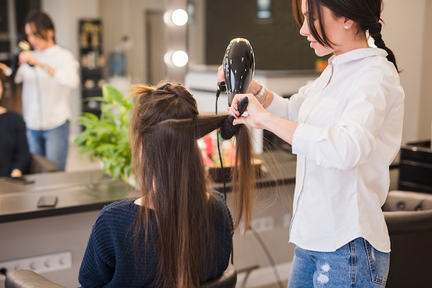 Brunette woman getting her hair done Premium Photo