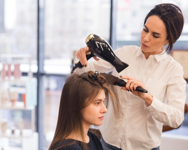Brunette woman getting her hair dried Free Photo