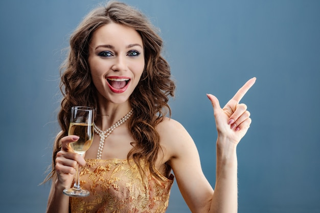 Brunette woman in golden dress and pearl necklace with raised glass of champagne celebrates Premium Photo