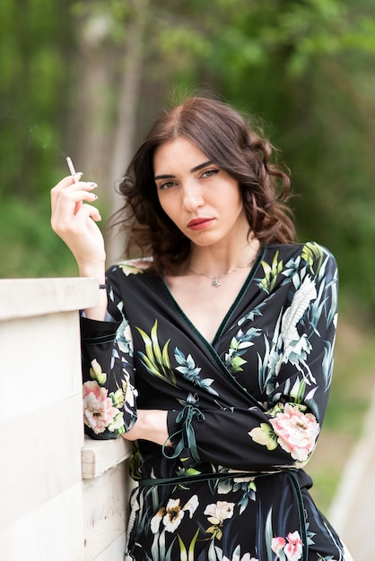 Brunette woman having a cigarette and looking at the camera Free Photo