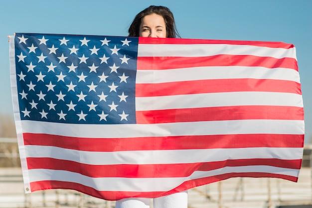 Donna castana che tiene la grande bandiera degli sua sopra se stessa Foto Gratuite