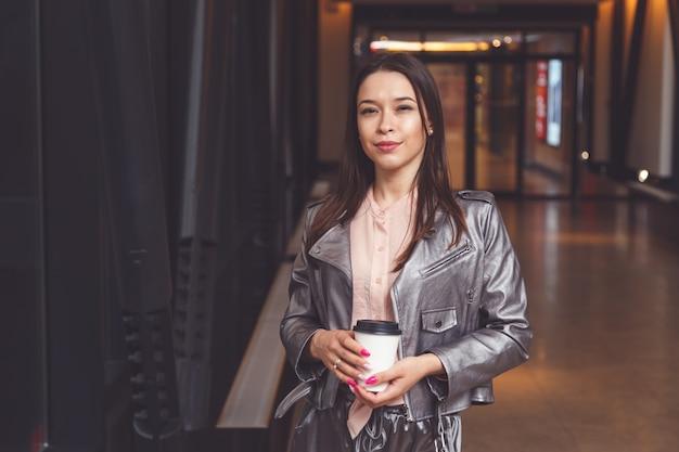 Brunette woman holding takeaway coffee Premium Photo
