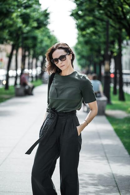 녹색 위쪽 및 검은 색 바지, 선글라스에 갈색 머리 여자. 프리미엄 사진