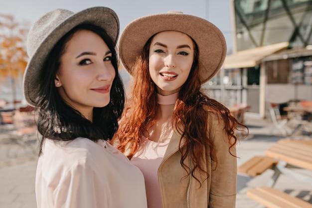 友人とポーズをとっている間、ふざけて肩越しに見ている帽子のブルネットの女性 無料写真