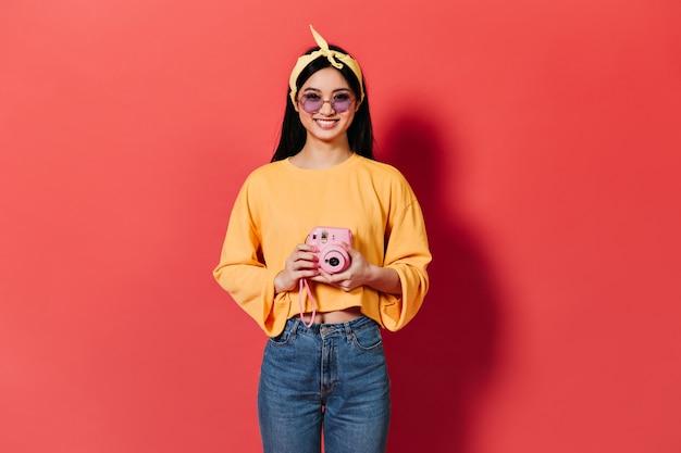 薄紫色のメガネのブルネットの女性は笑顔でピンクのフロントに写真を作っています 無料写真
