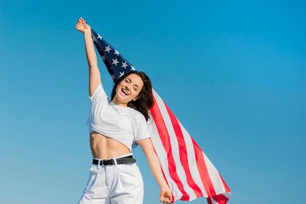 Брюнетка в белых одеждах держит большой флаг сша Бесплатные Фотографии