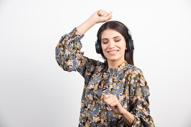 Donna castana che ascolta la musica e balla con l'espressione felice. Foto Gratuite