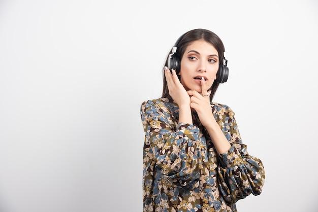 Donna castana che ascolta la musica in cuffia. Foto Gratuite