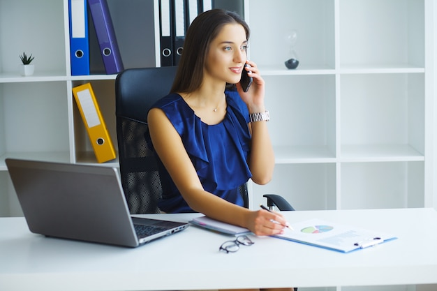 Brunette woman looking at phone while working Premium Photo