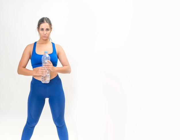 Brunette woman practicing fitness to lose weight and drinking water in a bottle Premium Photo
