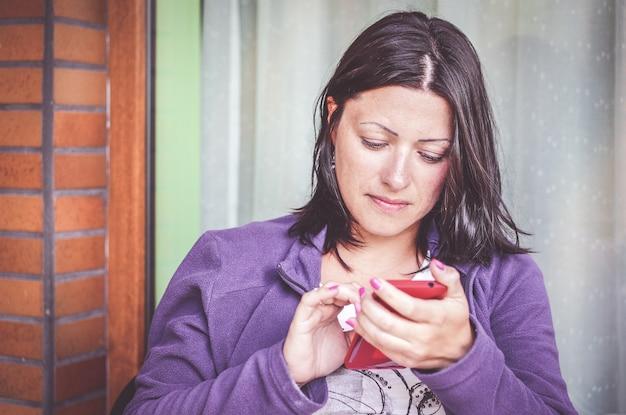 Donna castana in una giacca viola utilizzando uno smartphone Foto Gratuite