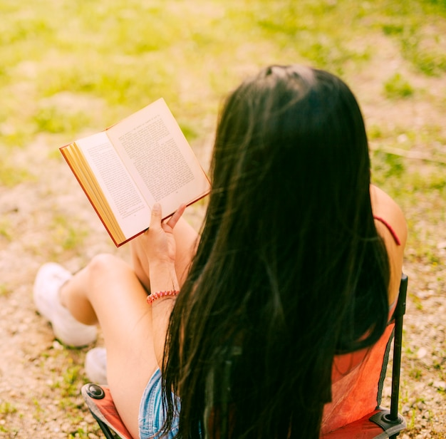 Brunette woman reading book in nature Free Photo