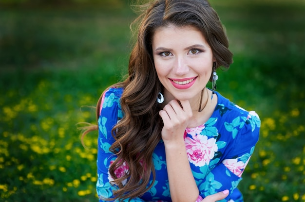 Brunette woman smiles in a summer green glade with flowers Premium Photo