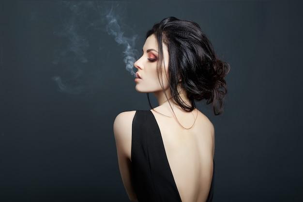 Brunette woman smoking on dark background Premium Photo