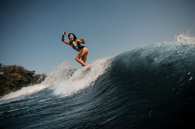 Brunette woman surfing on surfboard in sea Premium Photo