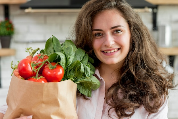 Brunette woman with a paper bag full of healthy food Free Photo