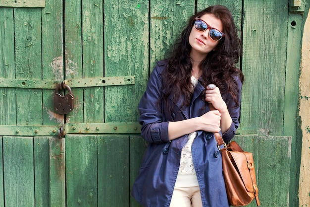 Brunette woman with sunglasses holding her brown handbag Free Photo