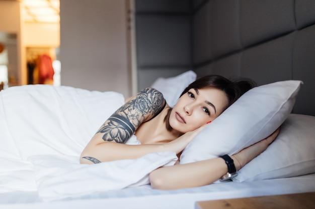 刺青のブルネットの女性は、ファッションのモダンなアパートメントで朝の枕のベッドで産む 無料写真