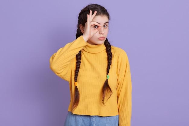 Брюнетка молодая женщина толкает знак ок и закрыла глаза, позирует на сиреневой стене Бесплатные Фотографии