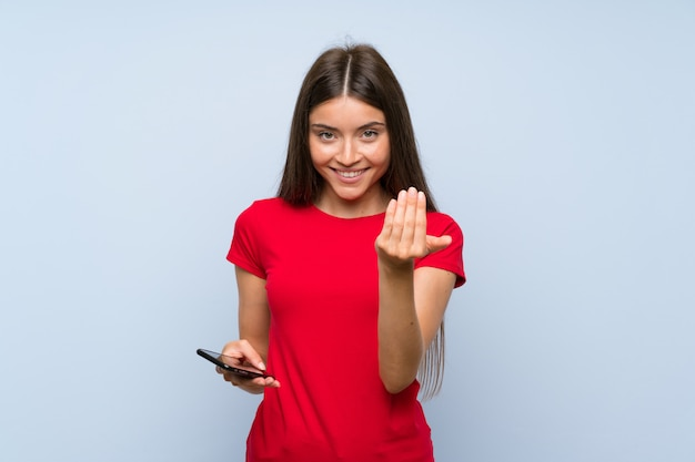 Brunette young woman with a mobile phone over isolated blue wall inviting to come with hand. Premium Photo