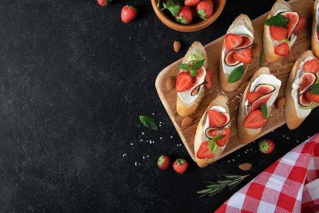 Брускетта со сливочным сыром, клубникой и инжиром Premium Фотографии