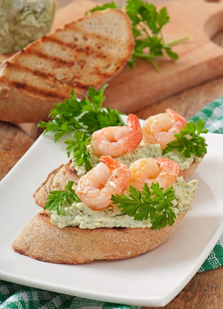 Bruschetta with a paste of green peas and shrimps Free Photo