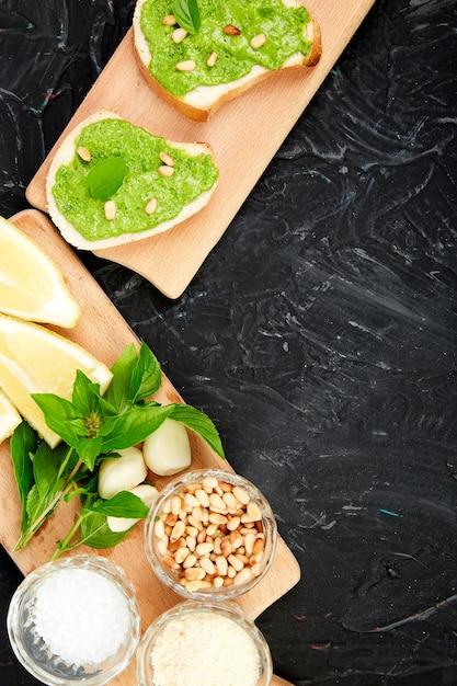 Брускетта с соусом песто, сыром пармезан и свежим базиликом Premium Фотографии