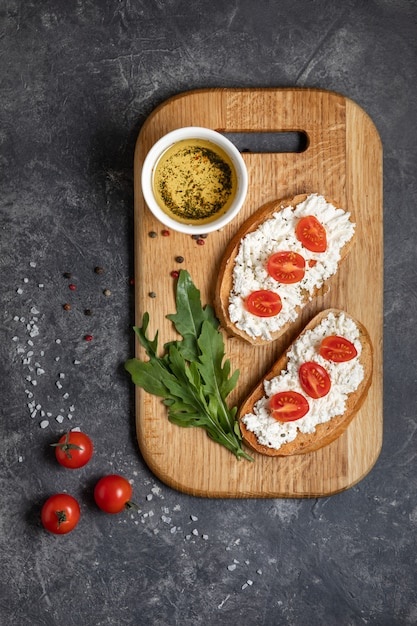 Bruschetta with roasted tomatoes and mozzarella cheese on a cutting board Premium Photo