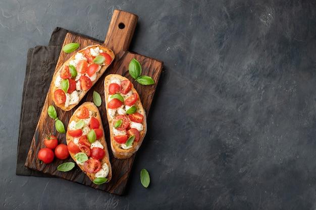 Bruschetta with tomatoes, mozzarella cheese and basil. Premium Photo