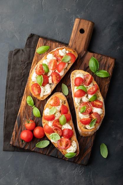 Bruschetta with tomatoes, mozzarella cheese. Premium Photo