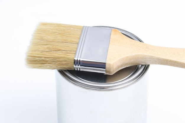 The brush lies on a can of white paint on a white surface Premium Photo