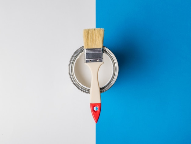 Brush on an open can of white paint on the border of two colors. execution of painting works. Premium Photo