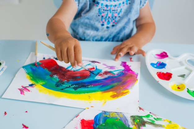 Brush with paint in the child's hand Premium Photo