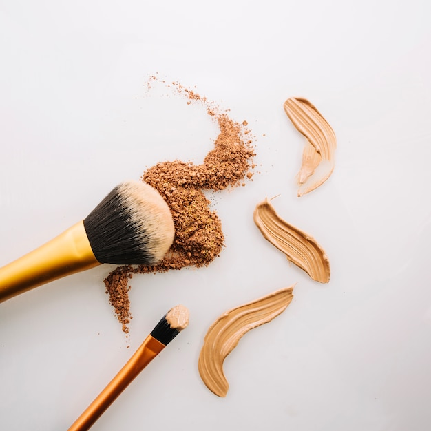 Brushes near powder and concealer Free Photo