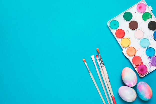 Brushes; painted easter eggs and plastic palette with water color on blue backdrop Free Photo