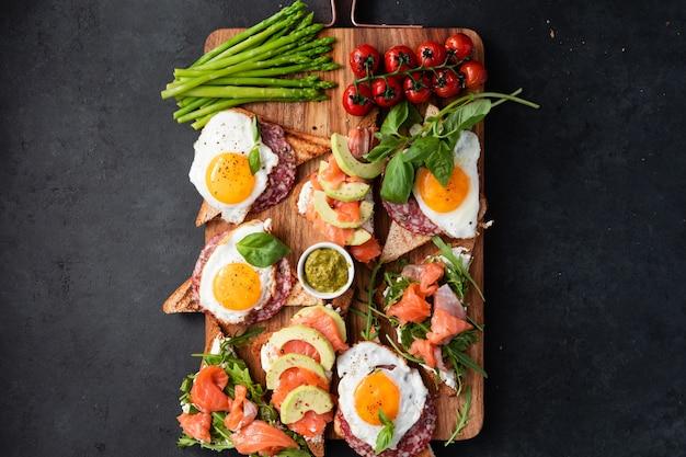 Brushetta or sandwich set on the board over black concrete Premium Photo