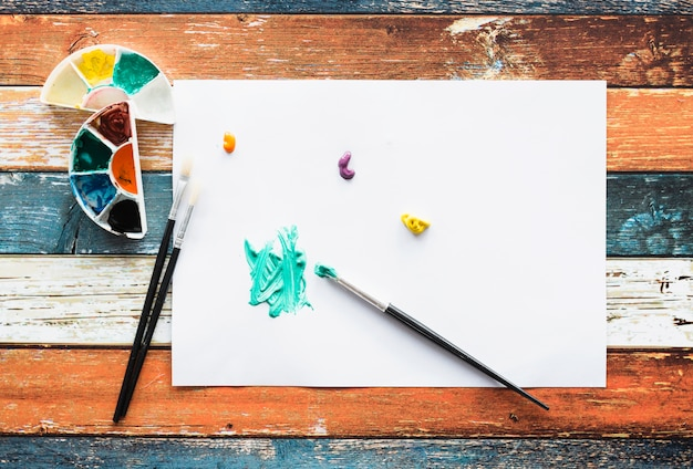 Brushstroke and paint stain on white page over wooden desk Free Photo