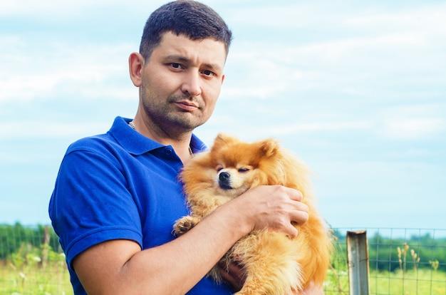 Жестокий привлекательный мужчина улыбается и держит в руках померанский шпиц. владелец обнимает собаку, вместе проводит свободное время на открытом воздухе. усыновление домашних животных. дружба человека и животного Premium Фотографии