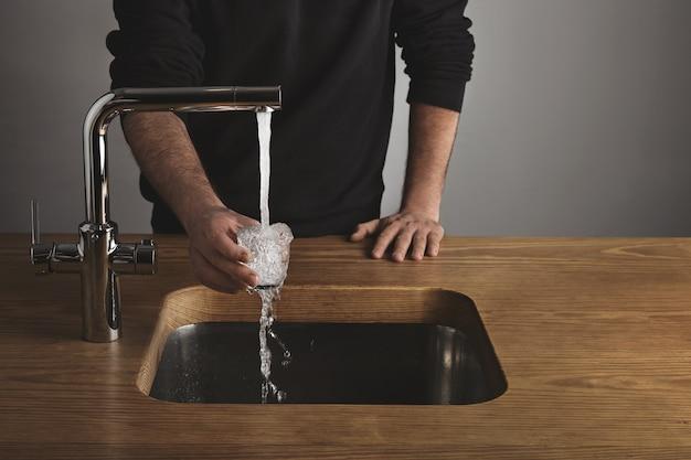 Barista brutale in sudore nero dietro un tavolo di legno spesso risciacqua un piccolo bicchiere trasparente con acqua sotto il rubinetto in metallo argentato nella caffetteria. gocce d'acqua dal vetro. Foto Gratuite