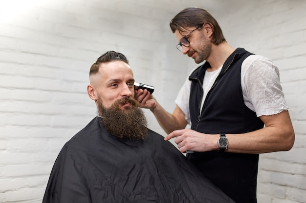 Brutal guy in modern barber shop. hairdresser makes hairstyle a man with a long beard. master hairdresser does hairstyle with hair clipper Premium Photo