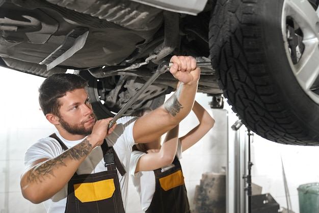 Brutal man repairing automobile with woman in autoservice. Free Photo