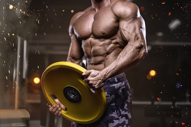 Brutal strong bodybuilder athletic men pumping up muscles with dumbbells Premium Photo